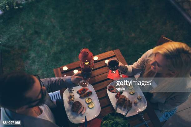 Tattooed Couple Having Romantic Backyard Barbecue Dinner With Proposal