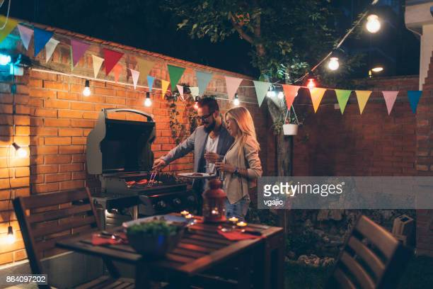 tattooed couple having romantic backyard barbecue dinner with proposal - grill concept stock photos and pictures