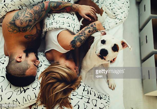 Tattooed Couple With Their Dog Sleeping