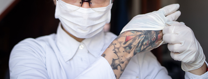 Tattooed doctor working 1218757998