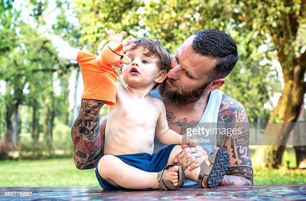 Tattooed Father and Son Playing with Puppet
