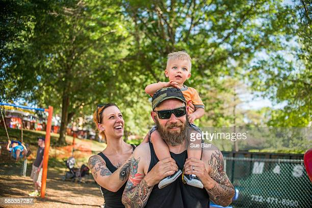 Tattooed father carrying baby boy on shoulders looking at camera smiling