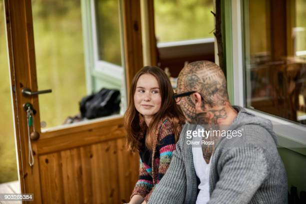 Tattooed father looking at daughter on a houseboat