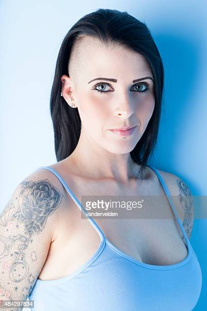 tattooed girl wearing a pastel blue dress - half shaved hairstyle stock photos and pictures