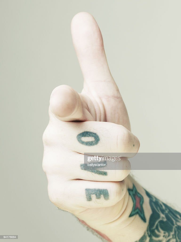 Tattooed hand making gun shaped gesture. : Stock Photo
