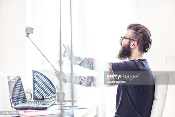 Tattooed hipster taking selfies in office with selfie stick