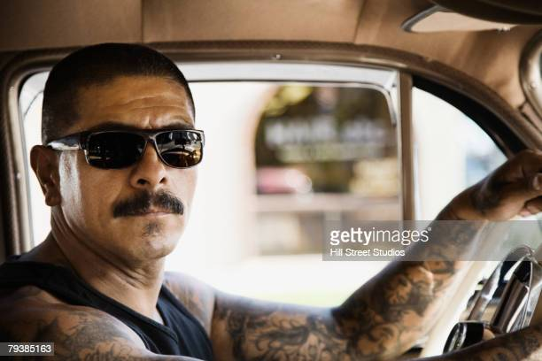 tattooed hispanic man driving car - low rider stock pictures, royalty-free photos & images