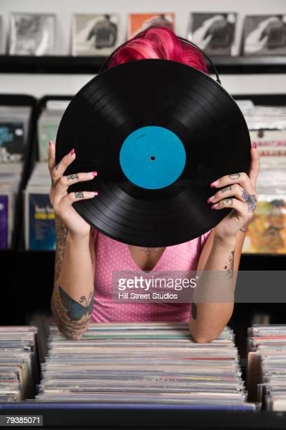 Tattooed Hispanic woman holding record album