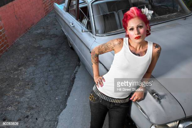 tattooed hispanic woman leaning on car - low rider stock pictures, royalty-free photos & images