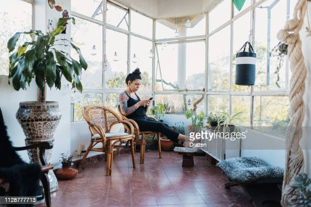 tattooed latina millennial woman using phone at home - simple living stock pictures, royalty-free photos & images