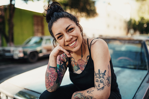 Tattooed Latina smiling outdoors and sitting on car hood 1168110319
