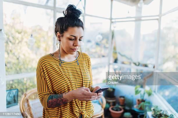 latina tatuada con teléfono inteligente - mujeres mexicanas fotografías e imágenes de stock