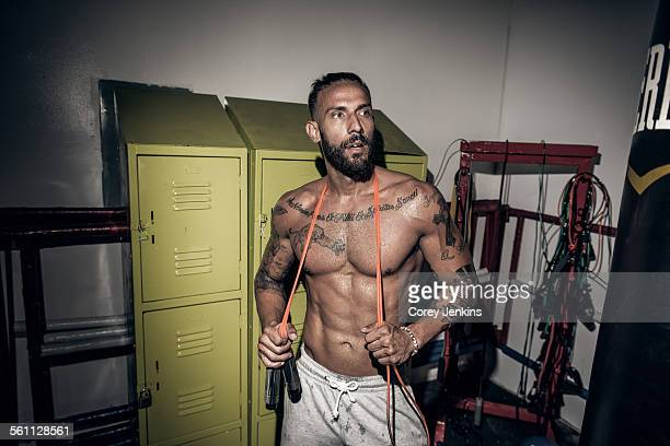 Tattooed male boxer with skipping rope in gym