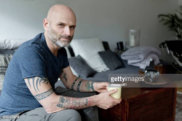 tattooed man at home sitting on couch, drinking coffee - three quarter length stock pictures, royalty-free photos & images