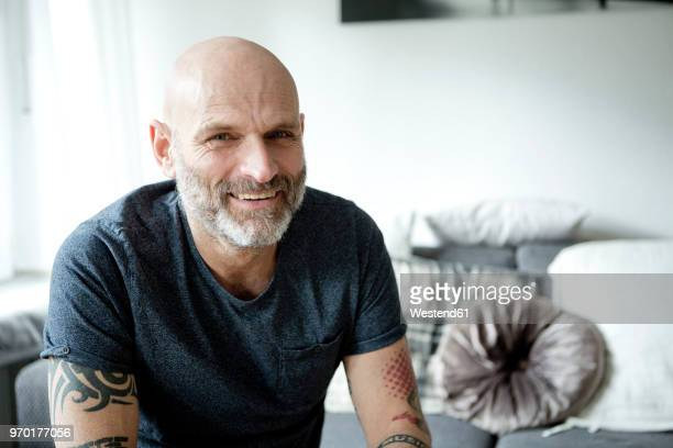 tattooed man at home sitting on couch - ヘアロス ストックフォトと画像
