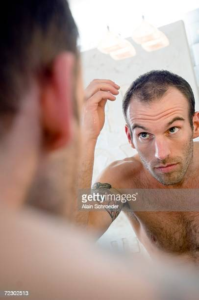 Tattooed man, bare-chested, looking in bathroom mirror
