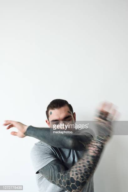 tattooed man beating the air - printed sleeve stock pictures, royalty-free photos & images