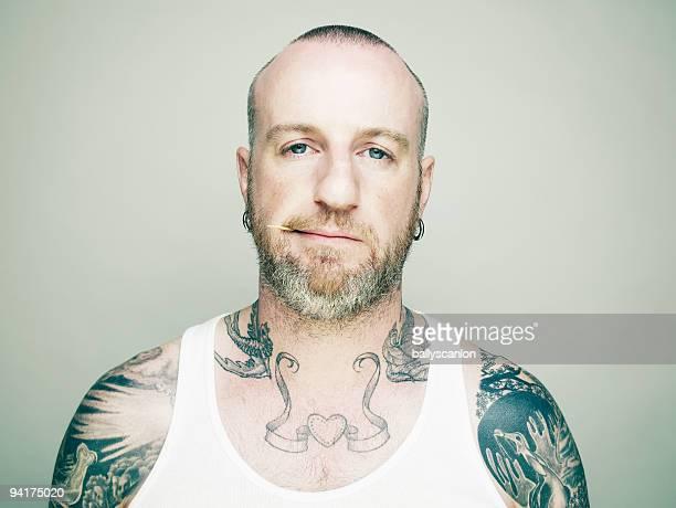 Tattooed man chewing toothpick.