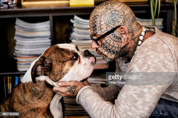 Tattooed man face to face with his dog