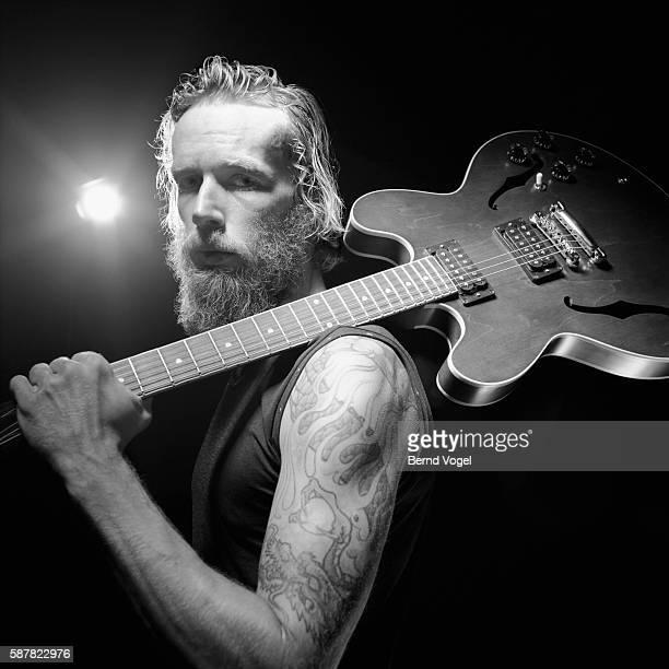 tattooed man holding guitar - musiker stock-fotos und bilder