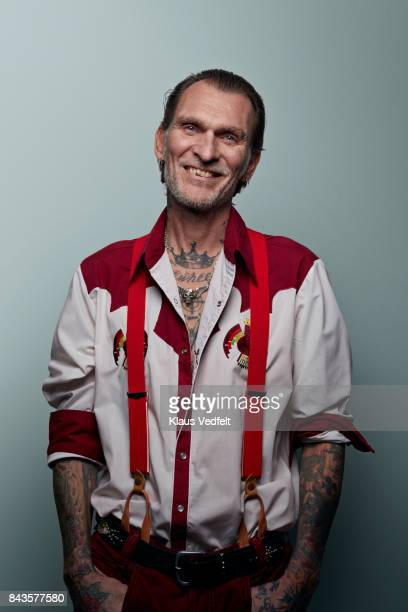 Tattooed man in red and white outfit, laughing to camera