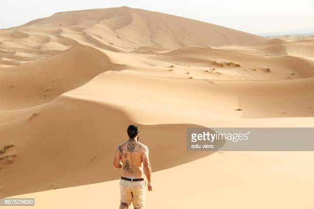 tattooed man running on the desert - merzouga stock pictures, royalty-free photos & images