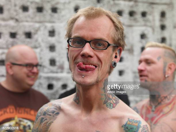 tattooed man showing split tongue - body piercings stock pictures, royalty-free photos & images