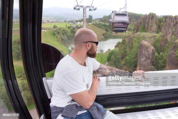 Tattooed man traveling by cable car