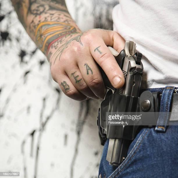 Tattooed man wearing holster with gun