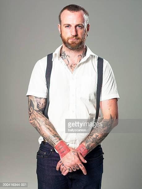Tattooed man wearing suspenders, portrait