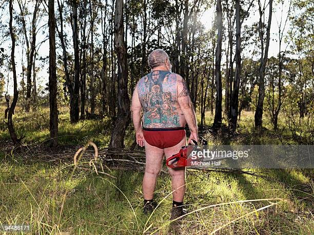 Tattooed man with chainsaw