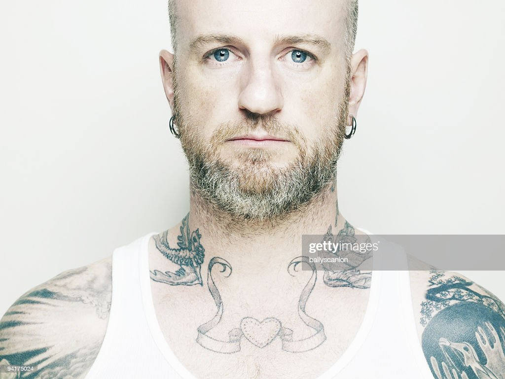 Tattooed man with serious face : Stock Photo