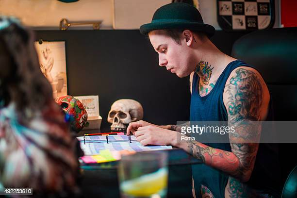 Tattooed man working in studio