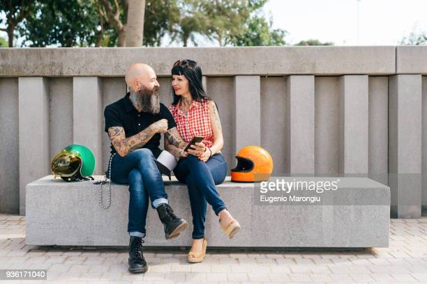 tattooed mature hipster couple sitting on concrete bench - bench stock pictures, royalty-free photos & images