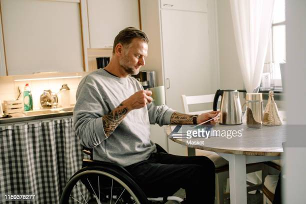 tattooed mature man reading mail while holding coffee cup on wheelchair at home - physical disability stock pictures, royalty-free photos & images