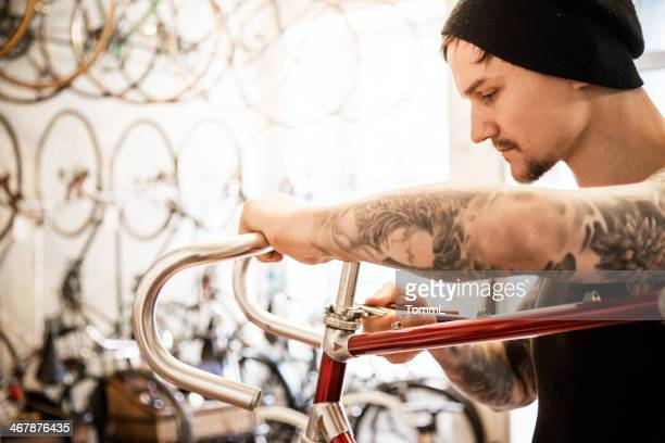 Tattooed Mechanic Working On Bicycle