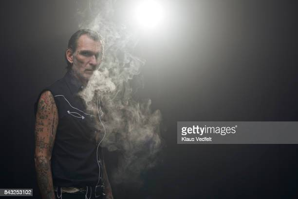 Tattooed mid aged man, smoking on vaper