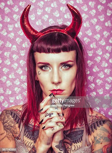 tattooed model with devil horns - devil costume stock photos and pictures