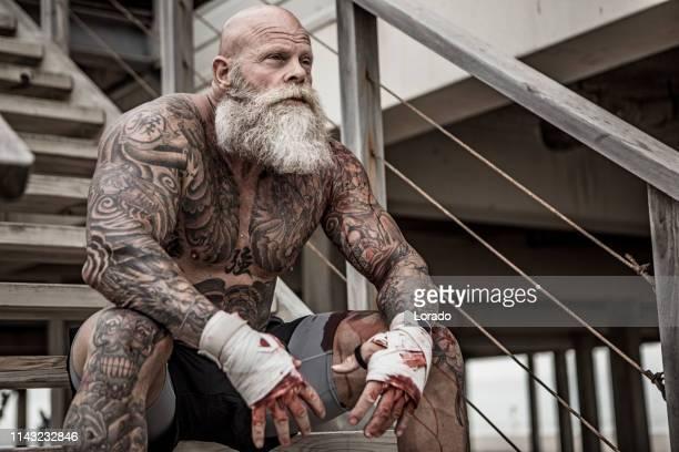 getatoeëerd senior bokser tijdens de gevechten workout - vechtkunst stockfoto's en -beelden