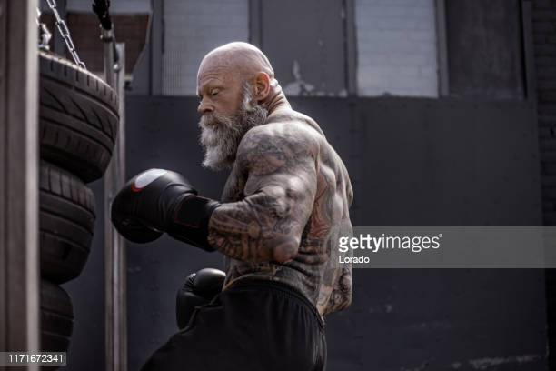 getatoeëerde senior boxer tijdens vechten workout - mixed martial arts stockfoto's en -beelden