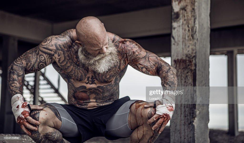 Getatoeëerde Senior Boxer tijdens training : Stockfoto