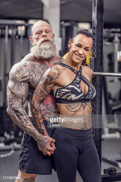 tattooed senior couple during gym workout - female bodybuilder stock pictures, royalty-free photos & images