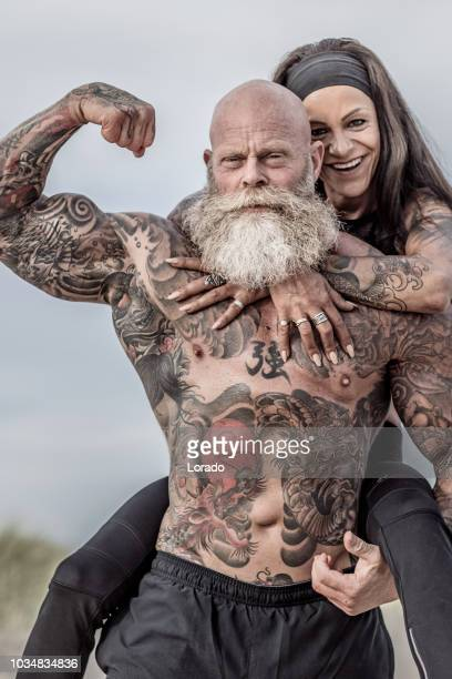 tattooed senior couple posing during workout - muscle men at beach stock photos and pictures