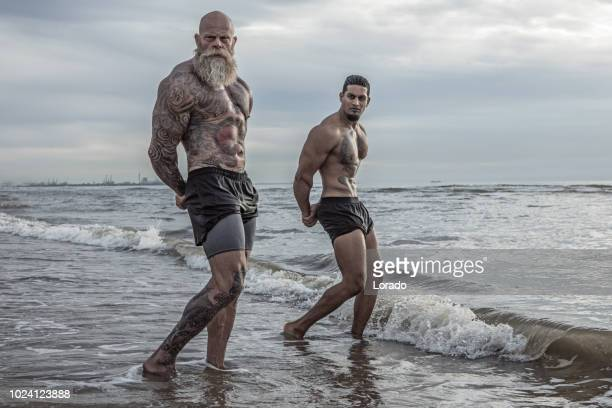 getatoeëerde senior man jongeman tijdens training coaching - beach stockfoto's en -beelden