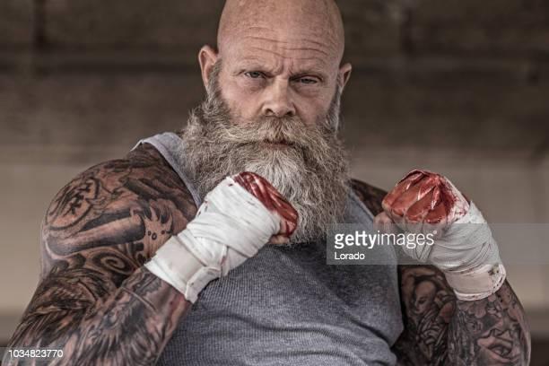 tattooed man senior tijdens strijd training - alleen seniore mannen stockfoto's en -beelden