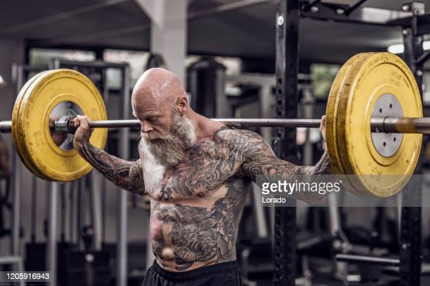 tattooed senior man during gym workout - handsome bodybuilders stock pictures, royalty-free photos & images