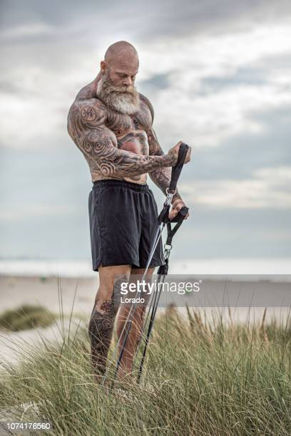 tattooed senior man during workout - muscle men at beach stock photos and pictures