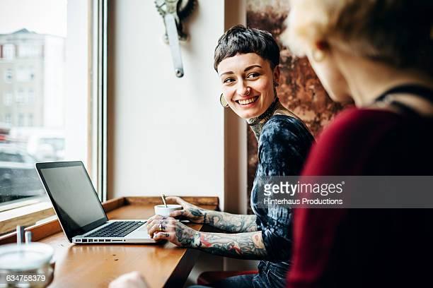 tattooed short-haired woman in a café - candid stock-fotos und bilder