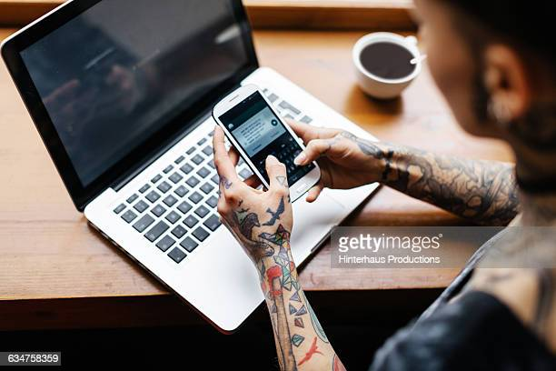 tattooed woman checking her smart phone - digital native stock pictures, royalty-free photos & images
