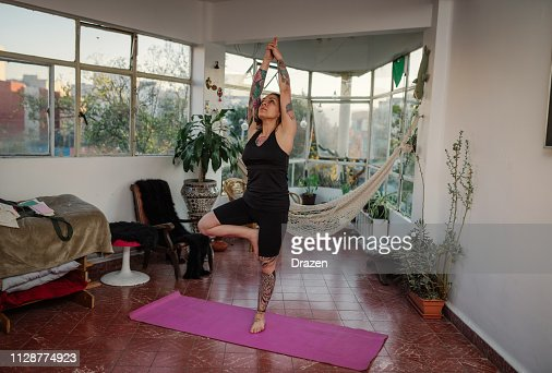 Tattooed Woman Doing Yoga At Home Warrior Pose High Res Stock Photo Getty Images